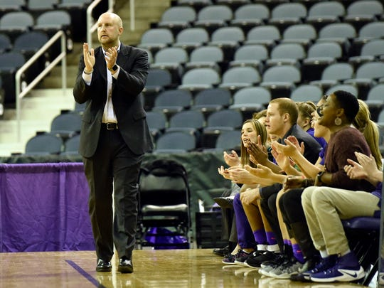 University of Evansville coach Matt Ruffing claps in front of his bench -- and rows of empty seats -- during a game last season at the Ford Center.