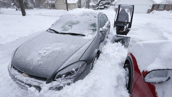 Sean Morgan clears snow from around vehicles in his driveway Monday morning in Appleton.