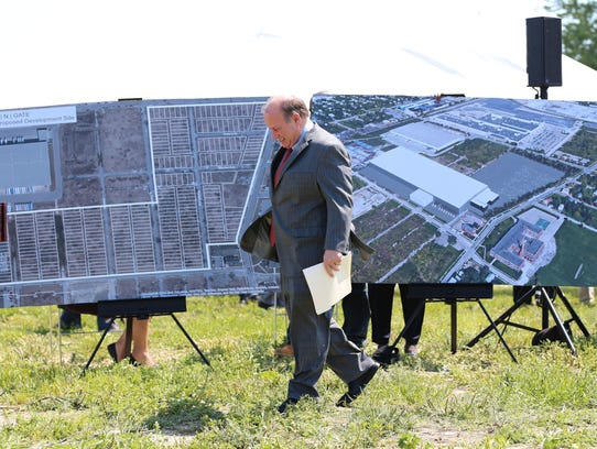 Detroit Mayor Mike Duggan walks across large renderings