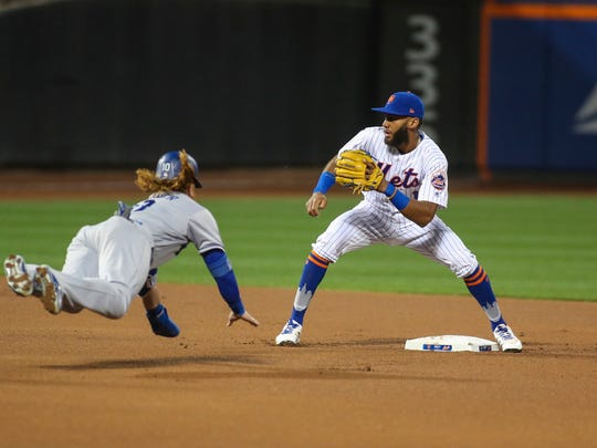 Aug 6, 2017; New York City, NY, USA; Los Angeles Dodgers third baseman Justin Turner (10) tries to beat the tag from New York Mets shortstop Amed Rosario (1) in the first inning at Citi Field.