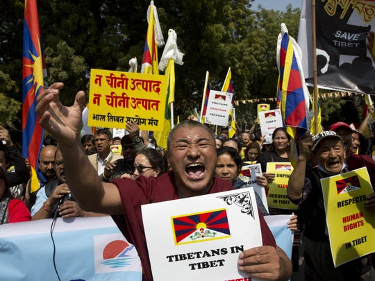 Exiled Tibetans shout slogans during a march to mark the 60th anniversary of the March 10, 1959, Tibetan Uprising Day, in New Delhi, India, Sunday, March 10, 2019.