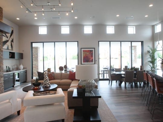 High, square windows help light the living space in a Verlaine home. The open floor plan joins the sitting area, which includes a working fireplace, with the kitchen and dining area.