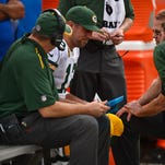 Green Bay Packers quarterback Aaron Rodgers (12) seeks medical attention on the bench in the first quarter during Sunday's game at Raymond James Stadium in Tampa, Fla. Rodgers hurt his calf after getting sacked.