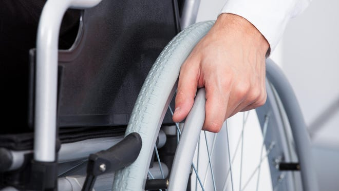 Close-up Of Businessman Sitting On Wheelchair In Office