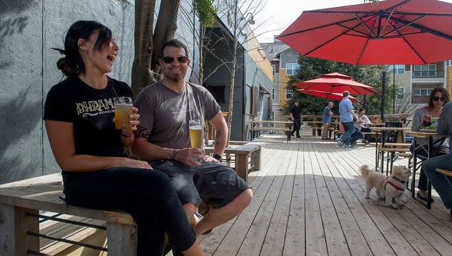 Server Hana Paulsen and Bhramari Brewhouse co-owner Josh Bailey sit under a tree on the brewery's large wooden deck where guests can enjoy their beer outside recently.