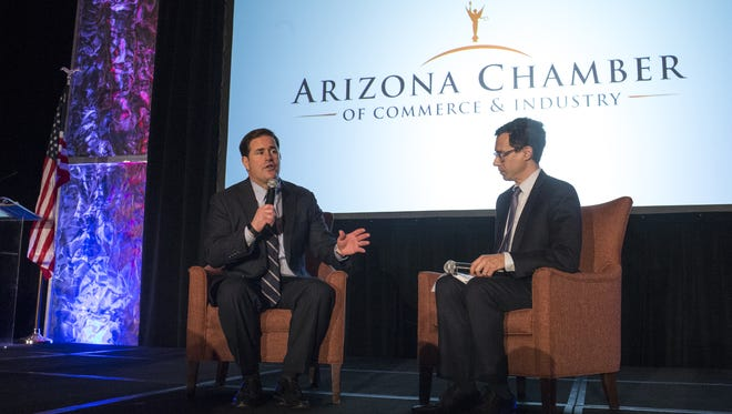Gov. Doug Ducey (left) answers questions for Glenn Hamer, CEO of the Arizona Chamber of Commerce, during a luncheon early this year. Both men expressed concern about the effect the U.S. Senate's proposed health-care bill would have on Arizona.