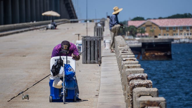 Joseph Hill, 75, searches through his cooler for fresh bait while fishing at the Bob Sikes fishing pier.