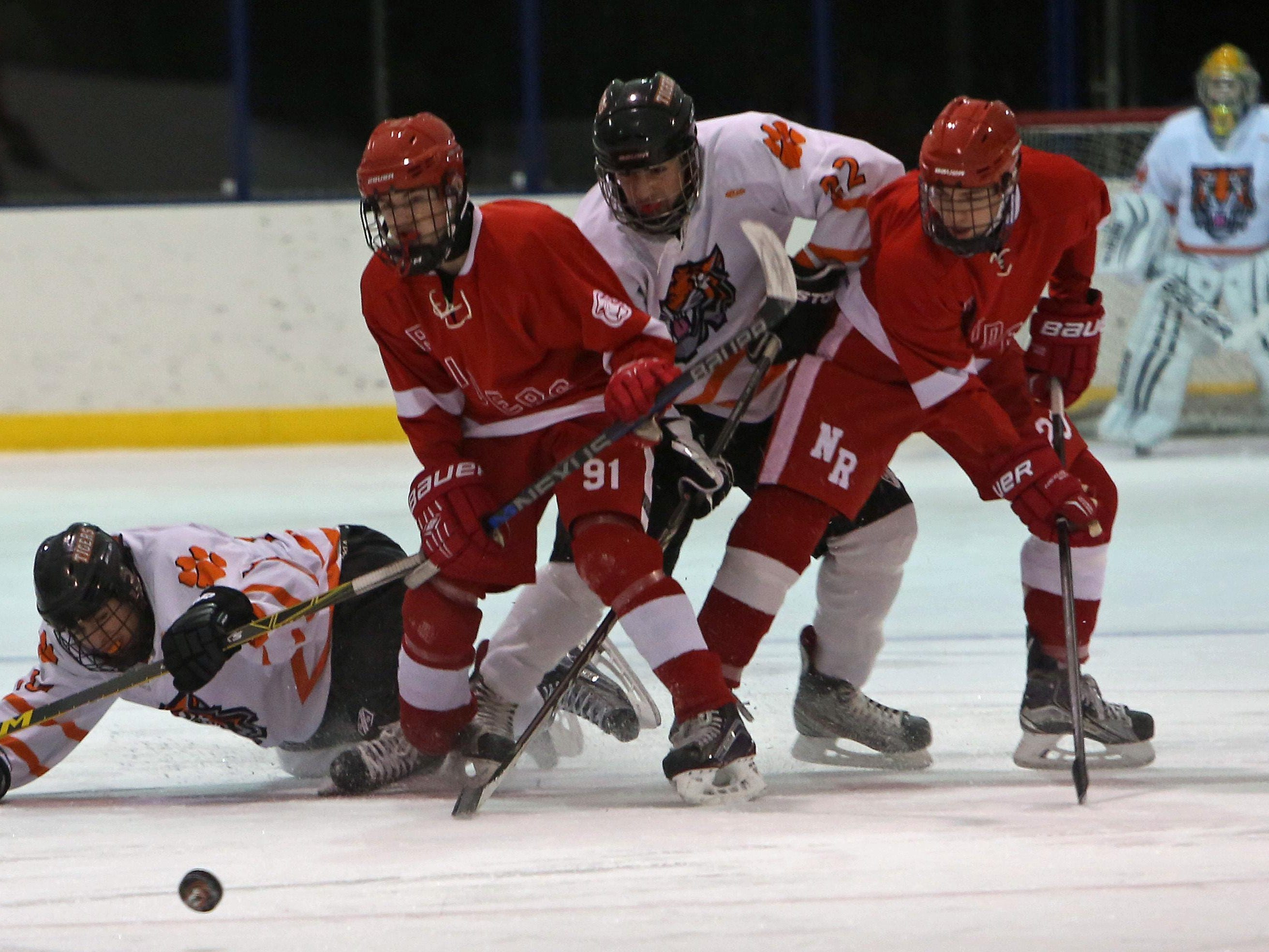 White Plains' Harry Seymour, left, and Chris Schiavone, second from left, battle for the puck with North Rockland's Chris Hilliard (91) during their game at Ebersole Ice Rink in White Plains Thursday. The game ended in a 4-4 tie.