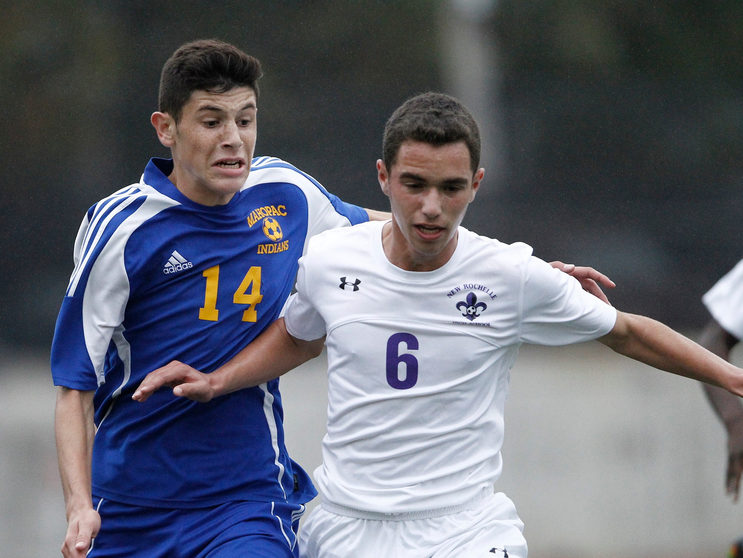New Rochelle's Andrew Sirola (6) and Mahopac's Augie Djerdjaj (14) battle for possession defends during the the boys soccer Class AA first round at New Rochelle High School in New Rochelle on Thursday, October 20, 2016. New Rochelle advances with their 2-0 win.