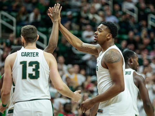 Michigan State's Nick Ward (44) high-fives teammates