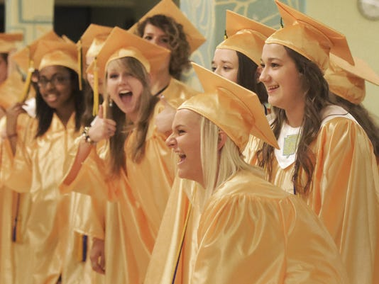 York Catholic seniors Shannon Moore, center, and Anne Lehr, right, joke with classmates before before commencement ceremonies at the school Friday, May 29, 2015. The school graduated 93 students.