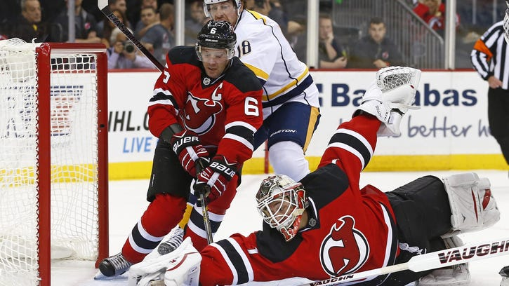New Jersey Devils goalie Keith Kinkaid (1) dives to make a glove save on a shot by Nashville Predators forward James Neal (18) as Devils defensemen Andy Greene (6) helps out during the first period of an NHL hockey game in Newark, N.J., Friday, Oct. 13, 2015.