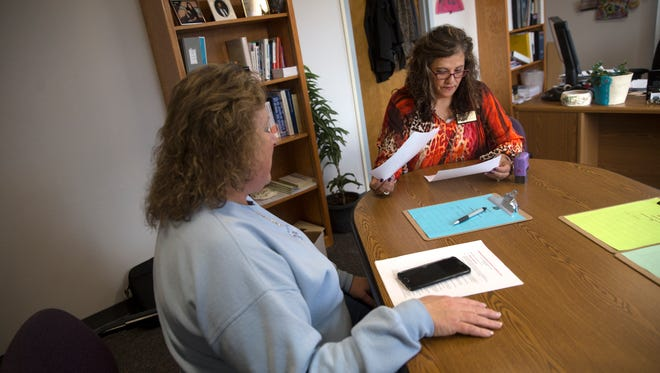 Aztec City Clerk Karla Sayler looks over incumbent City Commissioner Shari Rogers' filing paperwork on Tuesday at her office in Aztec City Hall.