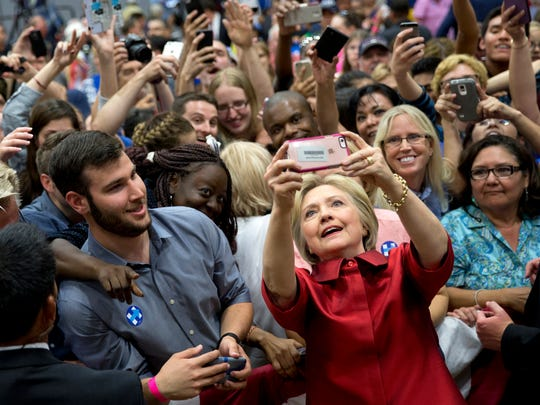 Democratic presidential candidate Hillary Clinton takes photos with supporters in the audience after speaking during a campaign event at Carl Hayden Community High School in Phoenix, Monday, March 21, 2016.