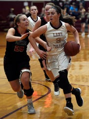 Karlie Keeney of Webster County dribbles towards the basket against  Shelby Jo Cecil of Daviess County during the second quarter of the game in Dixon Thursday.