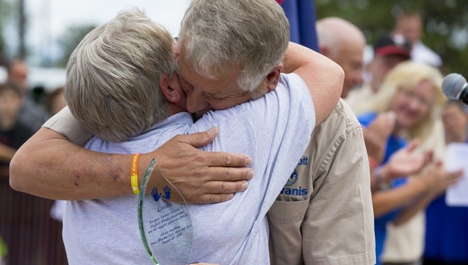 Linda Ballard, secretary of the Kiwanis Club of Prescott, hugs Carl Mueller during the grand opening of Kayla's Hands Playground in Prescott on August 27, 2016. Carl's daughter, Kayla, was an aid worker who was abducted and killed while being held captive by ISIS.