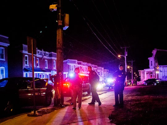 Members of the New Castle County Police Department stand near a stolen vehicle after a pursuit ended in the city of Wilmington on Sunday night, December 18, 2016.
