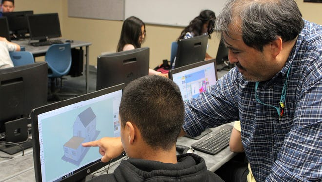 Lab instructor Adrian Gaytan checks a student's 3D model at Zia Middle School.