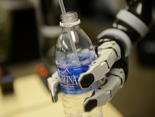 A robotic arm for Zeke Holmes picks up a water bottle