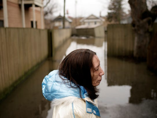 Blanca Rodriguez stands in the flooded driveway at