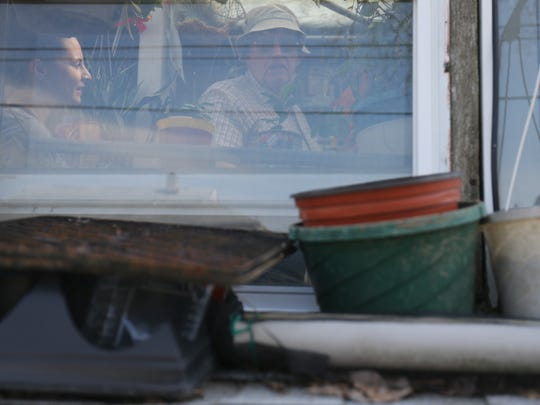 Richard Plucker takes News Journal health reporter Jen Rini through his greenhouse after rototilling the garden outside of his Newark home Thursday.