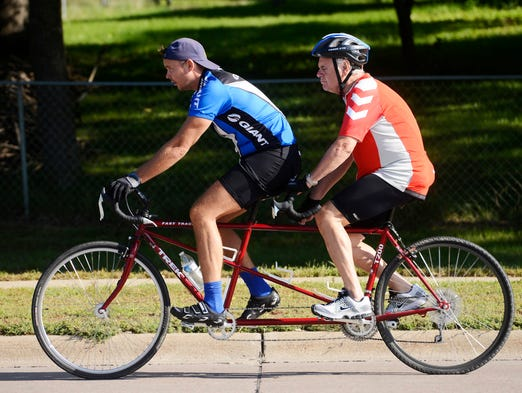 Harald Vik, 71, (in back) rides a tandem bicycle with his interpreter, Torben Loekaas west on 41st Street Friday, Aug 22, 2014. Vik, who is from Norway and blind and deaf was on a multi-day ride from Brookings to Lincoln, Neb when he was stuck by a car while northbound on Marion Road near Madison Street later Friday morning.