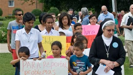 At right, sister Noemia Silva of the Missionary Sisters of Saint Charles Borromeo Scalabrinians walks with children and neighbors to Club Allure Chicago, a strip club, to protest its proximity to their convent, Wednesday, June 18, 2014.