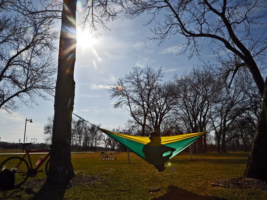Steven McClish of Des Moines sits in his hammock at Gray's Lake enjoying temperatures that were well above normal on March 11, 2016.