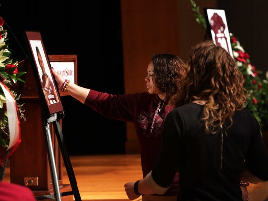 Roxanne Bruce touches the portrait of her son, MSU