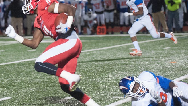 Rancocas Valley, Iverson Clement. 11, breaks a tackle against Millville's Bruce Williams, 6,  during the 2nd quarter of the game at Rancocas Valley.