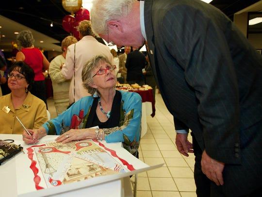 Brentwood artist Gail McDonald autographs a Brentwood