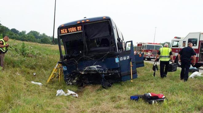 Emergency personnel respond to the scene of a bus accident Sunday, July 13, 2014, on Interstate 70 near Richmond, Ind.  Authorities say a Greyhound bus and another vehicle collided on the highway near Indiana's border with Ohio, killing one person and injuring 19 others.