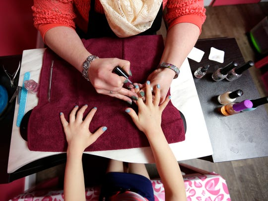 Brooklyn Swoboda, 6, gets a manicure by Emily Panzer, owner of Pure Glamour Nail Salon in Marshfield March 25, 2016.