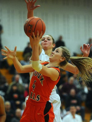 Washington's Maddie Wiley goes up for a shot while Roosevelt's Tagyn Larson tries to block the shot during their game at Roosevelt High School on Friday, Feb. 20, 2015.