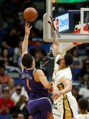 Feb 26, 2018: Phoenix Suns guard Devin Booker (1) shoots while defended by New Orleans Pelicans forward Anthony Davis (23) in the second quarter at the Smoothie King Center.