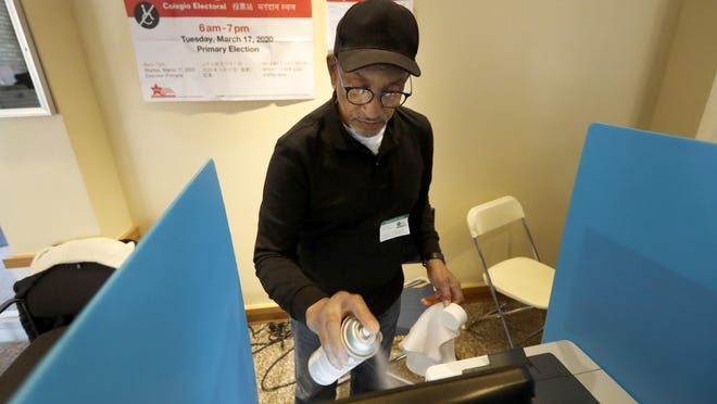John Davis, a polling judge volunteer, sanitizes an electronic voting machine screen amid concerns about the COVID-19 coronavirus at a polling place in the Bronzeville neighborhood of Chicago, Tuesday, March 17, 2020.