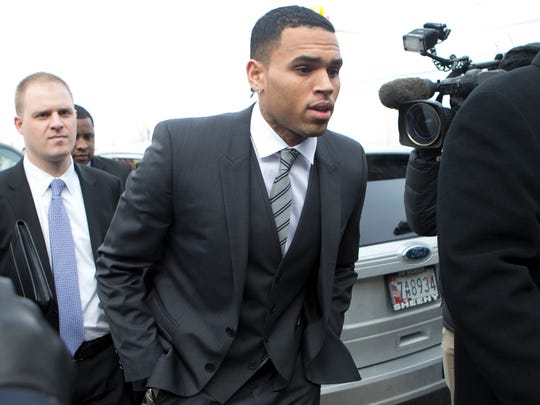 Chris Brown, right, arrives at the District of Columbia Superior Court in Washington, for a status hearing in a case in which he's accused of hitting a man outside a Washington hotel.