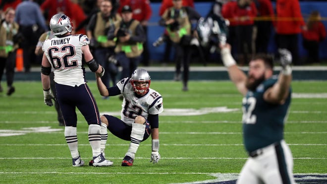 New England Patriots offensive guard Joe Thuney (62) helps quarterback Tom Brady (12) up after losing to the Philadelphia Eagles in Super Bowl LII at U.S. Bank Stadium.