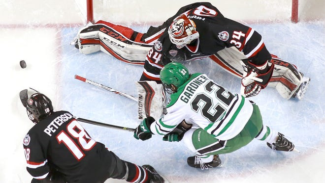 UND's Rhett Gardner reaches for the puck as St. Cloud State goalie David Hrenak makes a save in the first period at the Ralph Engelstad Arena.  At left is SCSU's Judd Peterson.