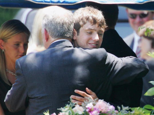 John Ramsey hugs his son, Burke, facing camera, at the graves of his wife, Patsy, and daughter JonBenet, during services for his wife at the St. James Episcopal Cemetery in Marietta, Ga in June 2006.