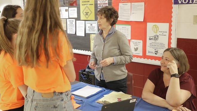 Colleen Neuman, left, and Sandy Lubow of the Coalition of Voting Organizations of Brown County (COVO) talks with De Pere High School students about voter registration ThursdayDe Pere.