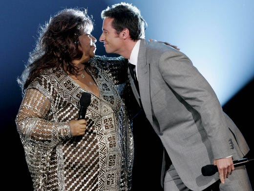 Host Hugh Jackman, right, leans to kiss Aretha Franklin
