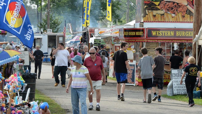 People circle the midway at the Albion Area Fair in Albion in this 2018 file photo.