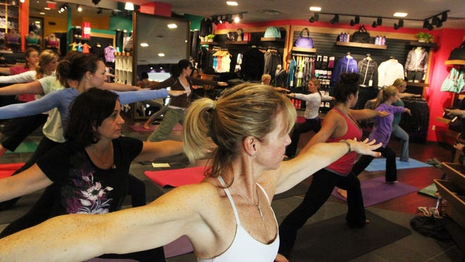 Yogis strike a pose during a class at the Lululemon Athletica store at Waterside Shops in Naples. The high-end fitness apparel company announced it is closing its downtown Fort Myers showroom March 19.