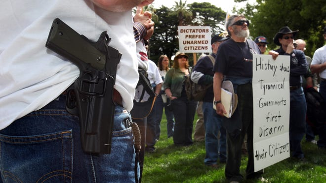 Ryan Burbridge, of Long Beach, Calif., left, wears a holstered unloaded pistol while attending a Second Amendment rally in Sacramento, Calif., Monday, April 19, 2010. More than 50 gun Second Amendment activists gathered to demonstrate their right to bear arms and protest a proposed measure the state Legislature that would ban gun owners from openly carrying unloaded guns in public. (AP Photo/Rich Pedroncelli)
