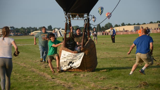 Joe Zavada holds on as other pilots and crews help stop his balloon during landing Thursday evening.