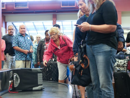 Passengers wait to retrieve the luggage after arriving