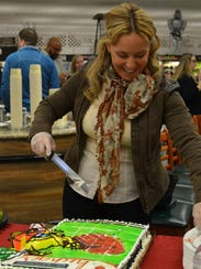 Dawn Meyers of General Mills cuts the cake at the ShopRite