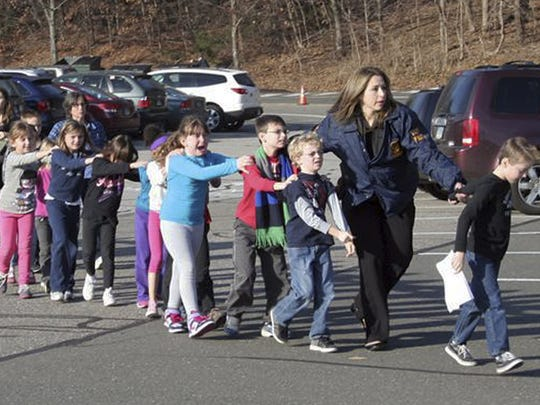 Connecticut State Police lead children from Sandy Hook Elementary School in Newtown following the 2012 shooting.