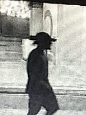 A man in a hat and a red long-sleeved shirt, shown here in a photo taken from surveillance camera, allegedly took a woman's purse on Dec. 23 in the Micronesia Mall parking lot. The woman, Cynthia Manibusan, was able to retrieve her purse with the help of a stranger.